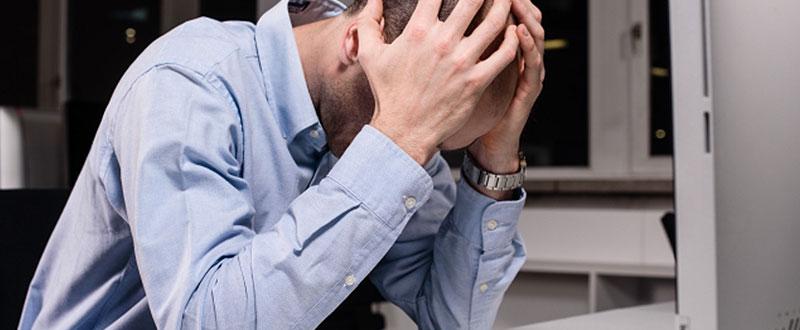 机で頭を抱える外国人
