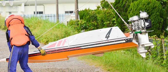 競艇レースの準備でボートを運ぶ選手
