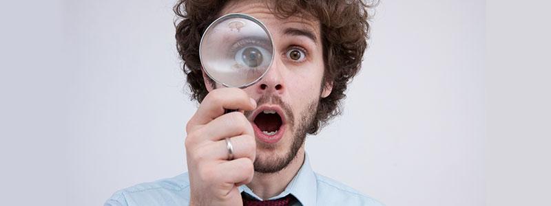 虫眼鏡をのぞく外国人男性